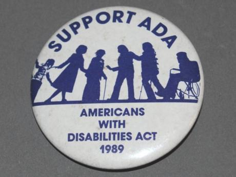 A white button with blue text reading: Support the ADA, Americans with Disabilities Act 1989. Between the two phrases in the middle of the button are silhouettes of six individuals some of whom are using mobility devices.