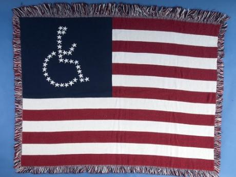 An image of an American flag woven lap blanket. Instead of the 50 white stars making up the upper left corner of the flag, the stars are arranged in the shape of the international symbol for accessibility- a figure in a wheelchair.