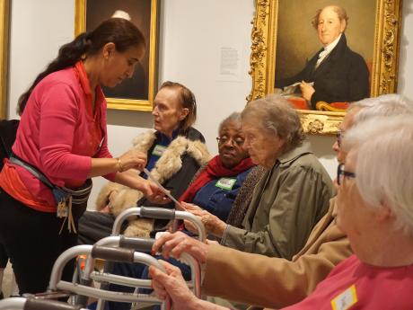 A woman stands in front of three elderly visitors holding an image in her hand. The visitors seated have walkers and are positioned in front of a portrait of a man in a gold frame.