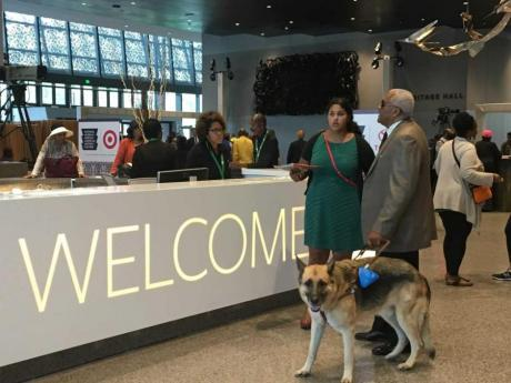 The Welcome Desk at the National Museum of African American History and Culture. On the right side of the frame, a tall man with dark brown skin is standing holding a service dog's leash in his hand. A woman with dark brown skin and a green dress stands next to him.